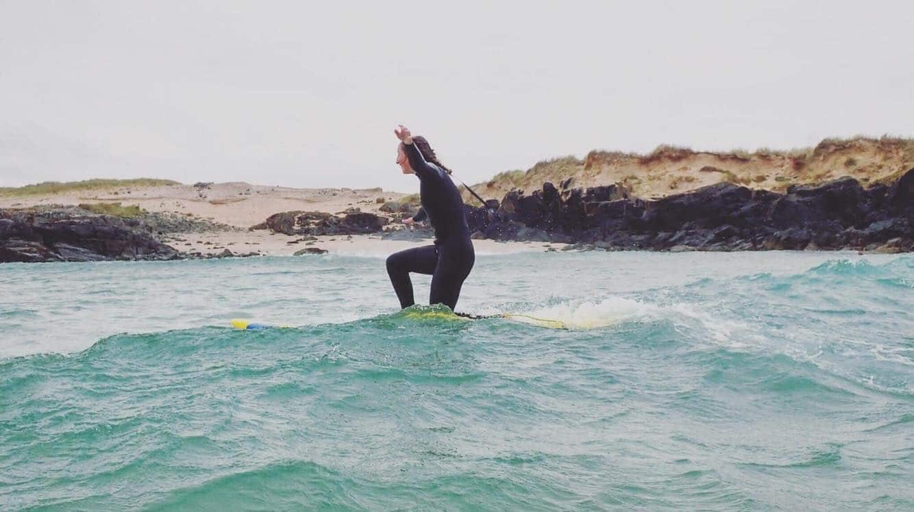 female surfer in the ocean leaning to surf