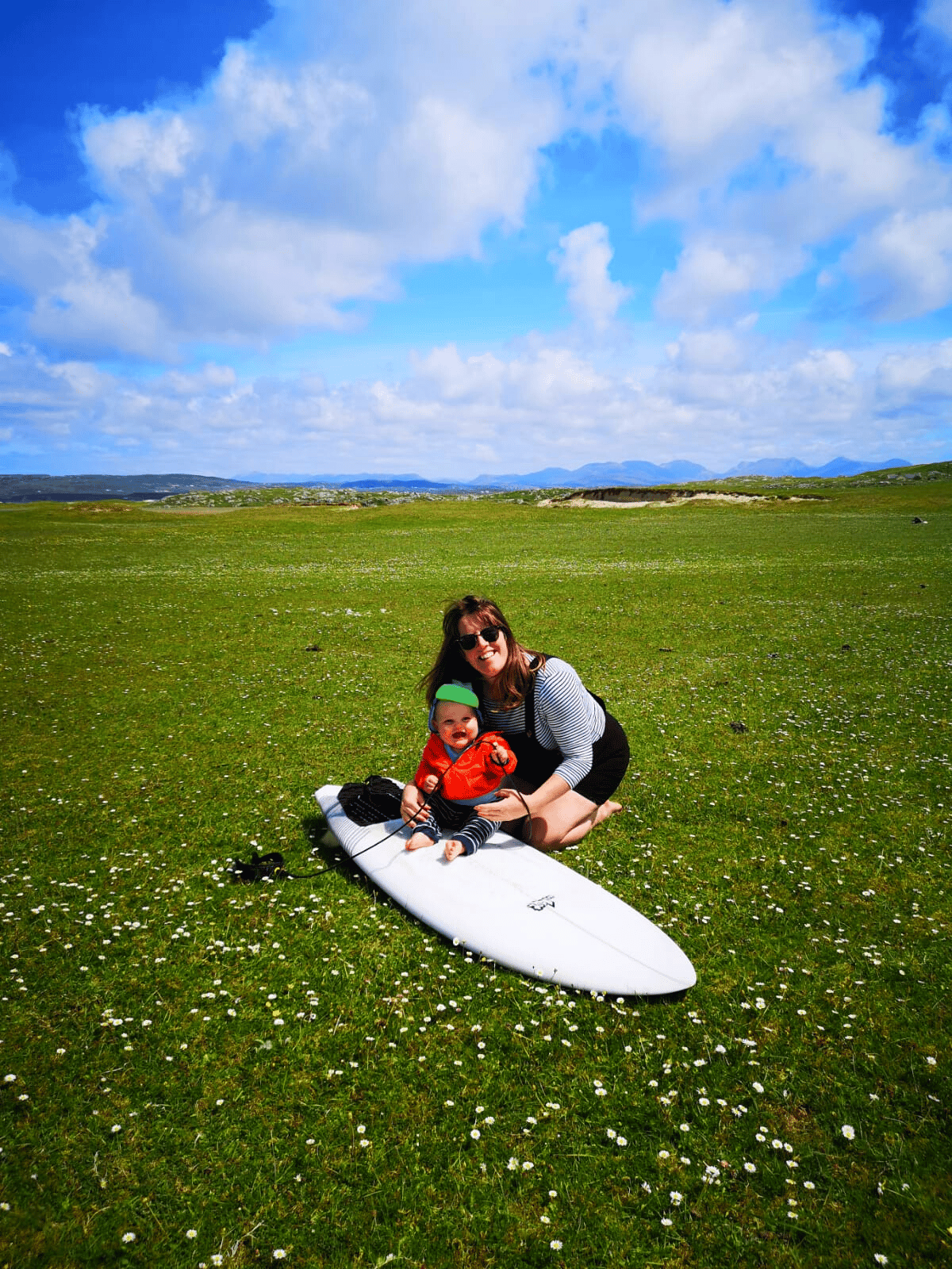 women kneeling on the grass next to a baby sitting on a large surfboard