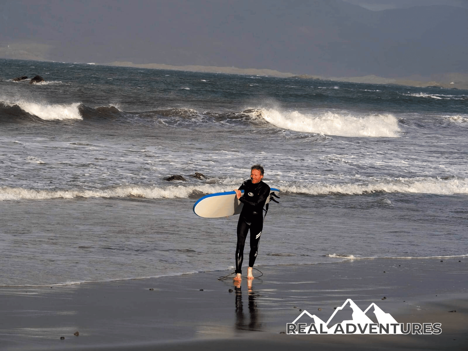 a man after a surf holding surfboard on beach with waves behind him